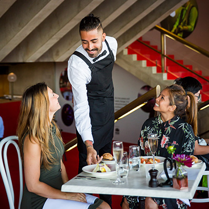 A waiter serves a witlof salad in the Northern Foyer of the Joan Sutherland Theatre at Sydney Opera House