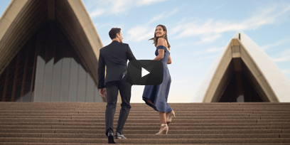 A couple walks towards Sydney Opera House with a play button on the image