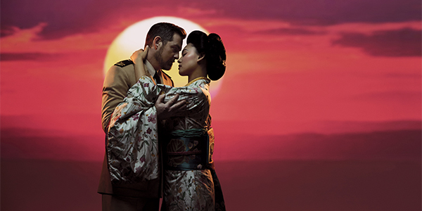 a man and a woman dressed as a geisha embracing in front of the sunset