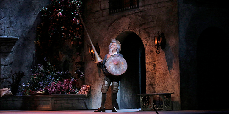 Don Quichotte bursts into the town square, lance and shield in hand