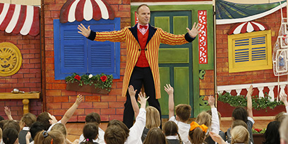 A performed in a costume stands in front of a group of school children with their hands up