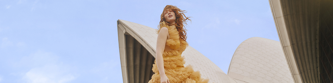 An opera singer wears an orange dress on the steps of Sydney Opera House