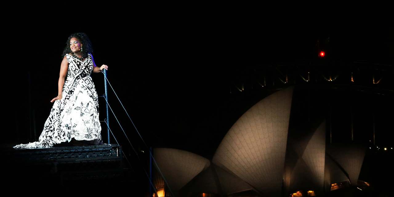 A woman stands on a platform in a long white dress in a performance of Aida. Sydney Opera House is in the background.