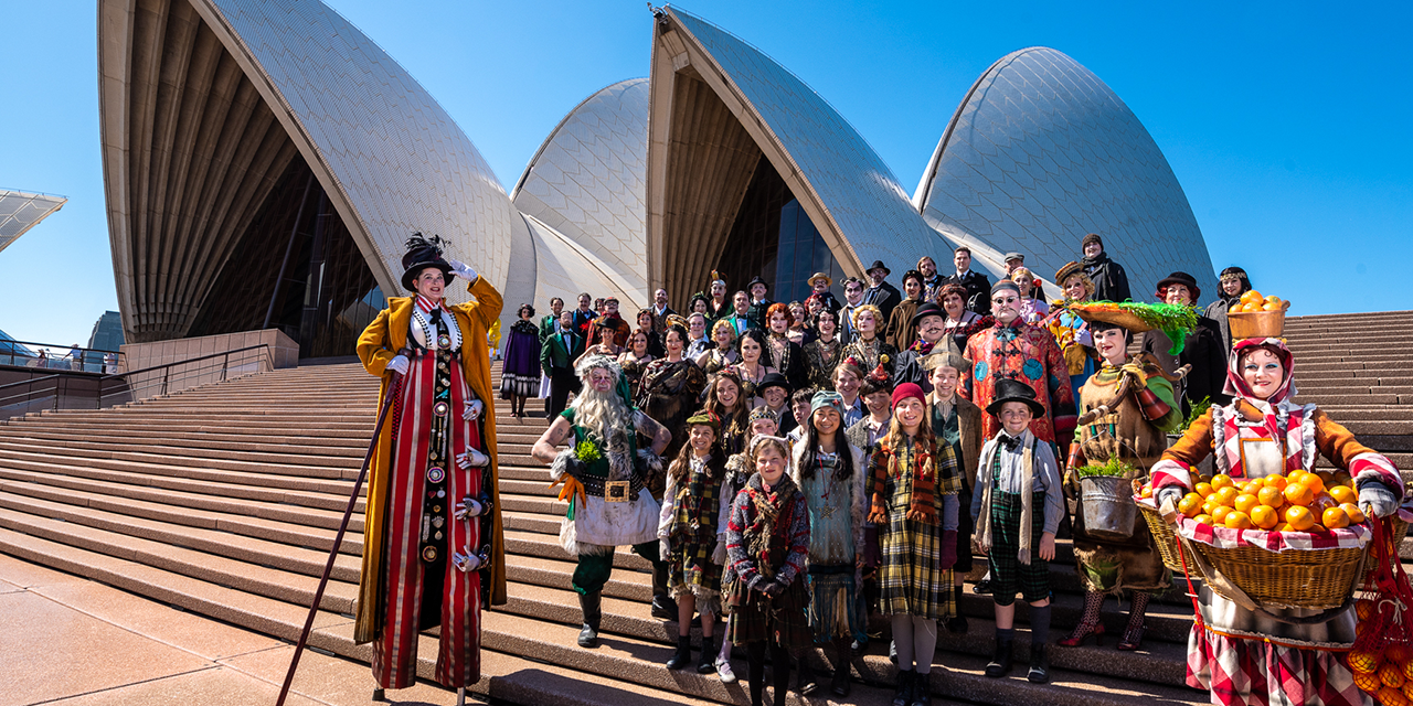 A group of performers in 1940s costumes stand on the steps of the Sydney Opera House