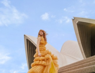 Opera singer in a yellow dressing singing on the steps of the Sydney Opera House