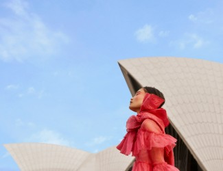 A woman in a pink dress walking towards the Sydney Opera House
