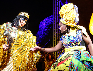 Two singers in a performance of Aida stand on stage holding hands.