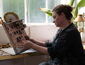 A woman sits examining a small set model of a terrace building.