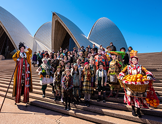 A group of singers stand on the steps of the Sydney Opera House.