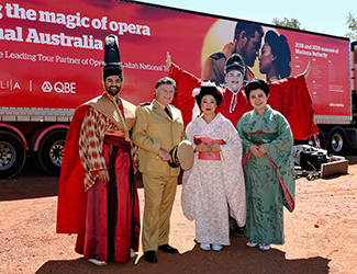 A group of people in Japanese costumes stand in front of a red truck