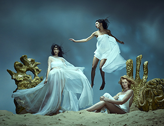 Three women floating at the bottom of the sea with gold coral
