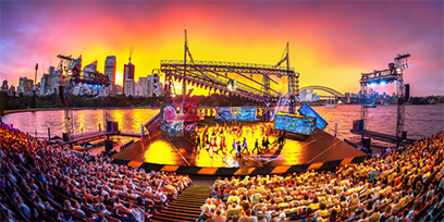 A large outdoor stage with Sydney Harbour in the background.