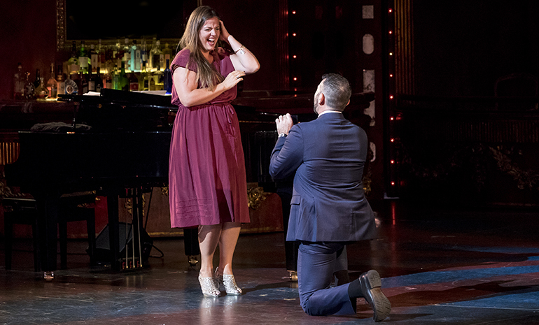 A man drops to one knee to propose to a woman on stage at the Sydney Opera House