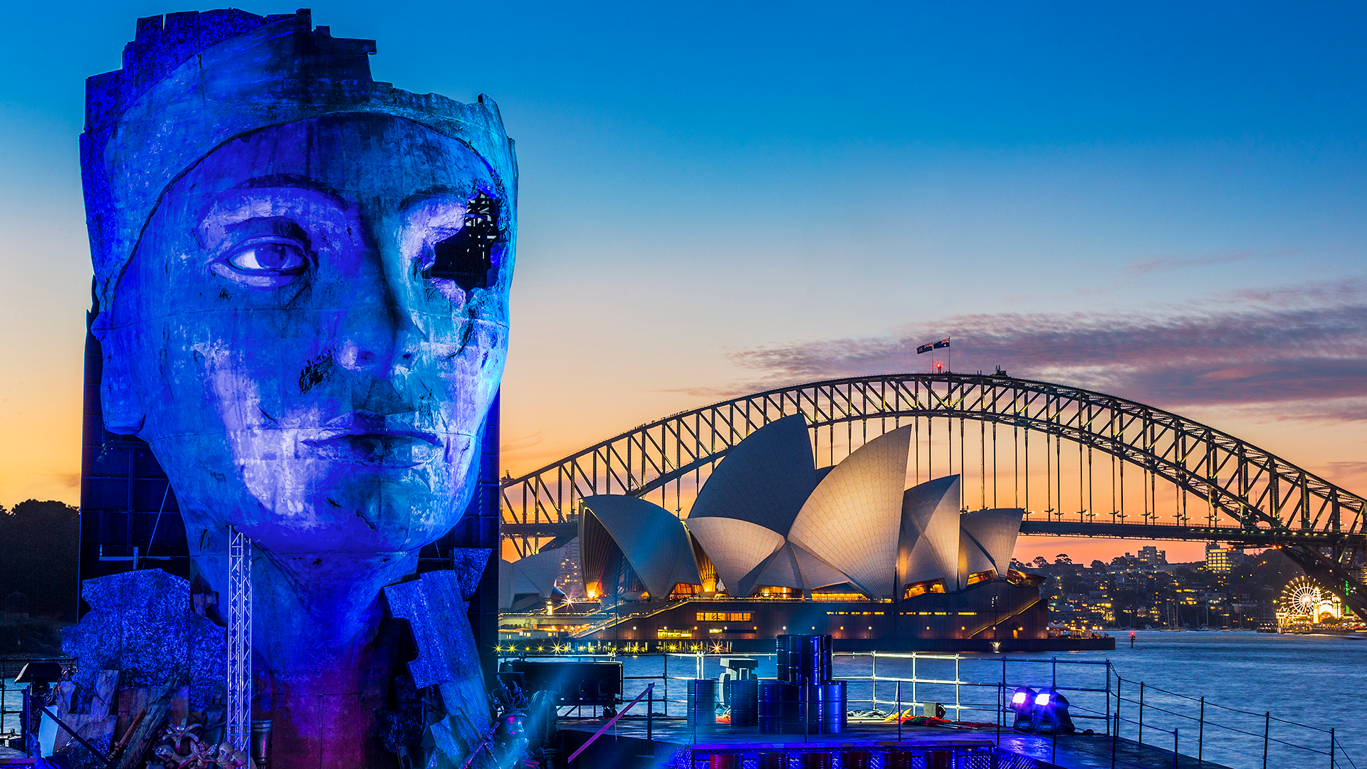 A giant bust of Egyptian queen Nefertiti stands in front of the Sydney Harbour Bridge and Opera House.