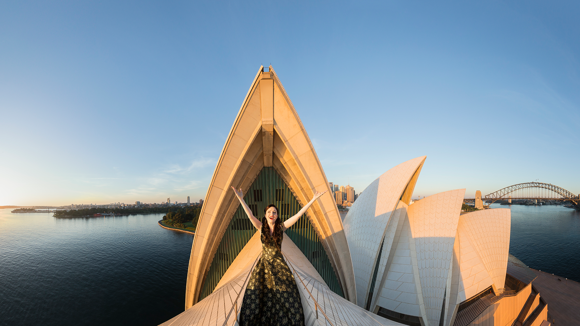 A woman stands atop the sails of the Sydney Opera House.