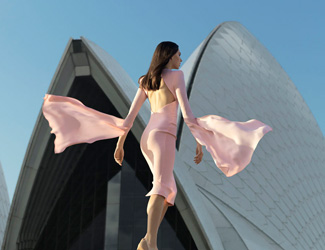 A beautiful woman in an Alex Perry designed pink dress walks up the stairs of the Sydney Opera House