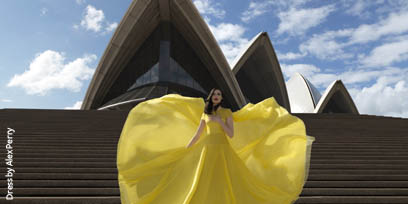 A soprano in a billowing yellow Alex Perry dress sings on the steps of Sydney Opera House