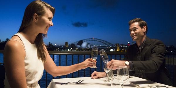 A couple clink glasses in front of Sydney Harbour.