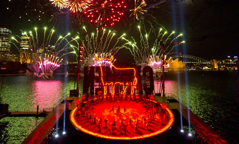 Fireworks explode over a neon bull outline on the Carmen on Sydney Harbour set