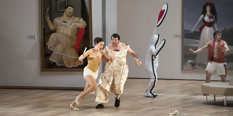 A man dressed in a period dress and a woman chase around the stage