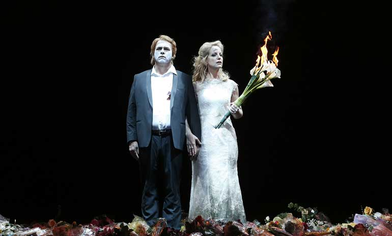A bridegroom in white face paint and a bride with ash smudged on her forehead stand together. She holds a flaming bouquet