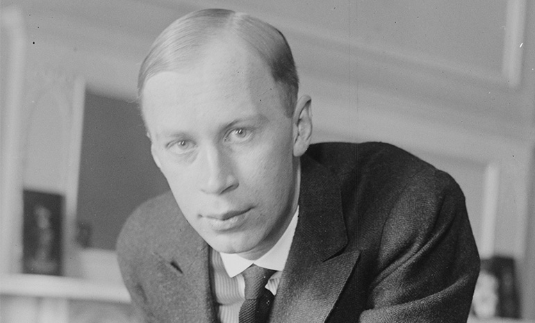 A photograph of Sergei Prokofiev leaning over a chair