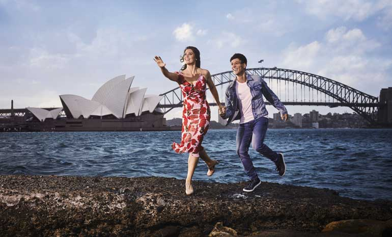 A girl and boy lean forward, hands outstretched on the edge of Sydney Harbour