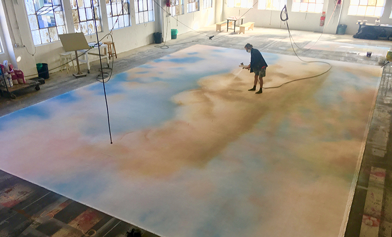 A scenic artist painting a floor