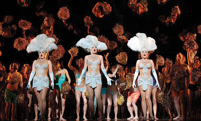 Rhinemaidens dressed as showgirls stand in front of a crowd of people holding golden pompoms.