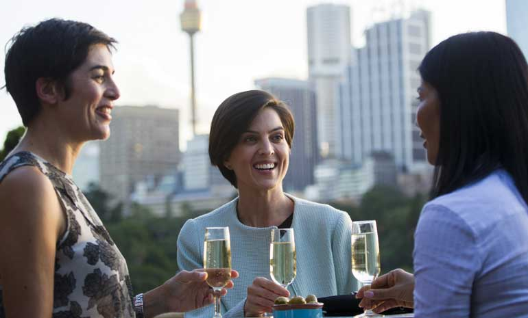 Three women toast with Champagne against the city skyline