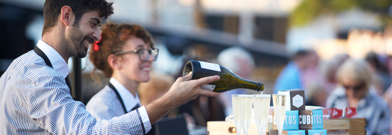 Two waiters pour sparkling wine from a pop-up small bar at Handa Opera on Sydney Harbour