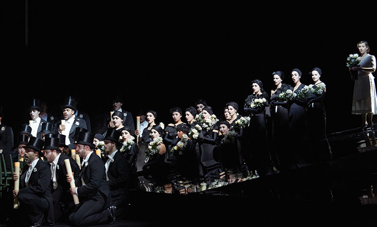 Men in top hats and suits and women in black evening gowns hold flowers and candles.