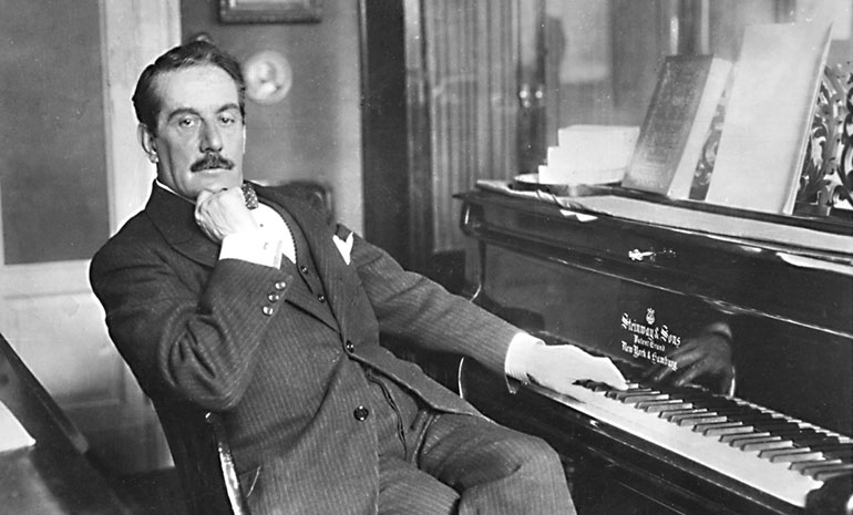 A photograph of Puccini sitting at his piano