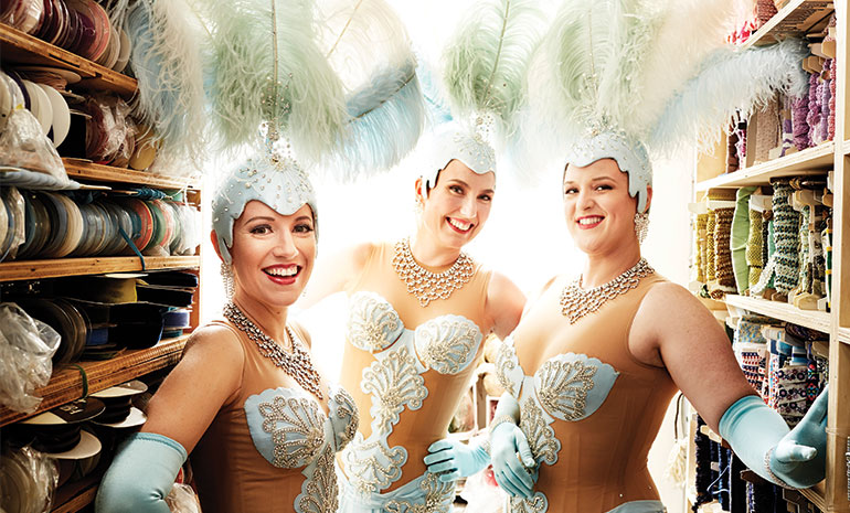 Singers in showgirl outfits pose in the ribbon shelves in Opera Australia's wardrobe department