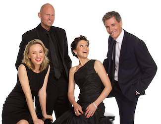 Four singers stand dressed in black against a white background, smiling at the camera