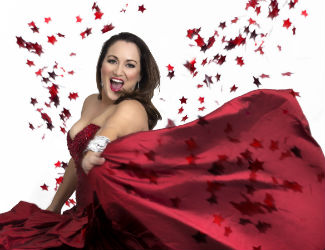 A woman wears a red gown smiling at the camera surrounded by confetti