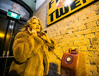 Woman stands dressed in a fur coat on the phone in a bar