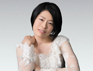 A woman in a white lace top sits at the black table looking at the camera