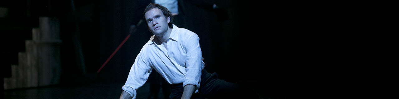 Michael Fabiano crouches on stage, dressed as a young Faust in a white flowing shirt