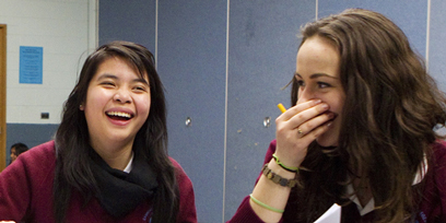 Two secondary school students, laughing